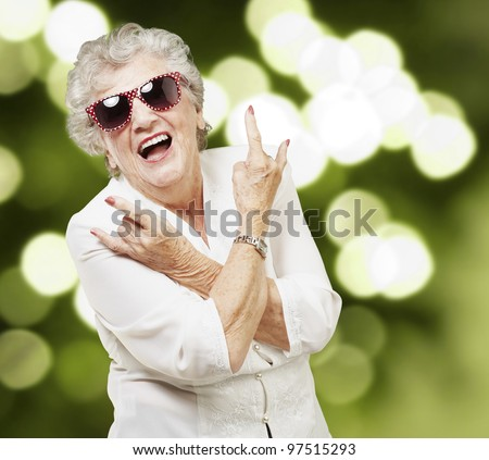 portrait of senior woman doing rock symbol against a abstract background