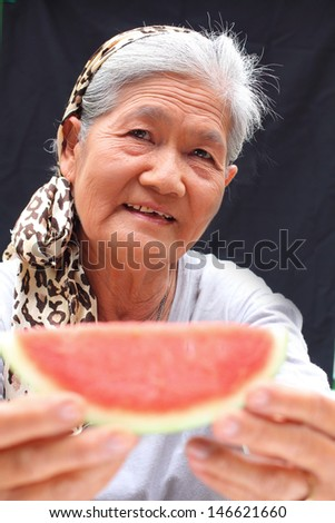 Portrait of senior woman eating melon