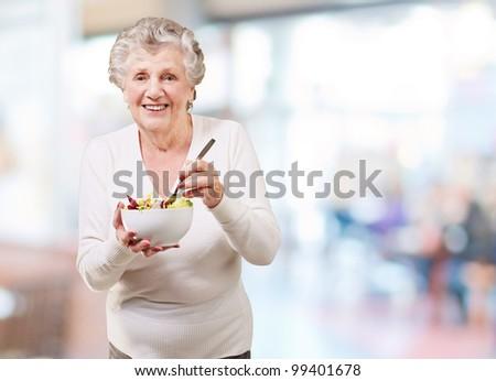 portrait of senior woman eating salad indoor - stock photo