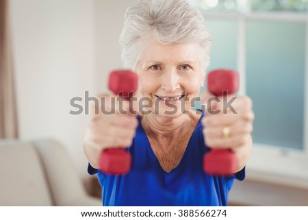 Portrait of senior woman exercising with dumbbells at home - stock photo