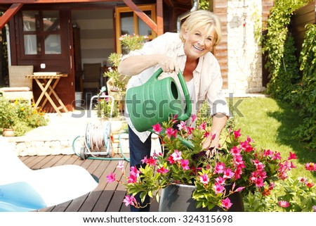 Portrait of senior woman gardening at home. Retired female cares of plants while standing in her beautiful garden.