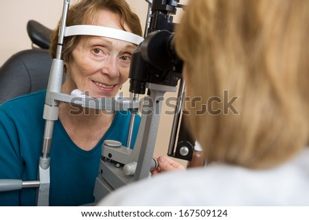 Portrait of senior woman having eye test with slit lamp in store - stock photo