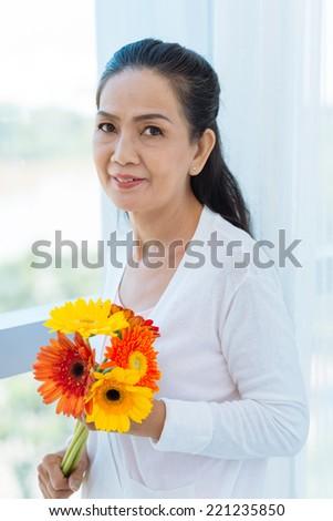 Portrait of senior woman holding a bouquet of gerberas - stock photo