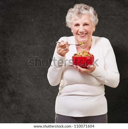 portrait of senior woman holding a cereals bowl against a grunge wall - stock photo