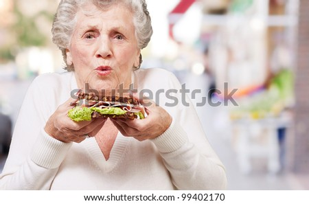 portrait of senior woman holding a delicious sandwich at street - stock photo