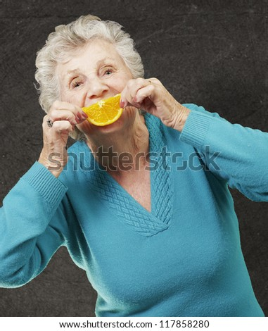 portrait of senior woman holding a orange slice in front of her mouth against a grunge wall - stock photo
