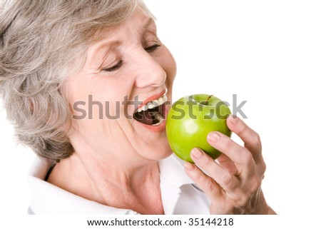 Portrait of senior woman holding an apple and eating it - stock photo