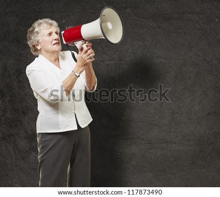 portrait of senior woman holding megaphone over grunge wall - stock photo
