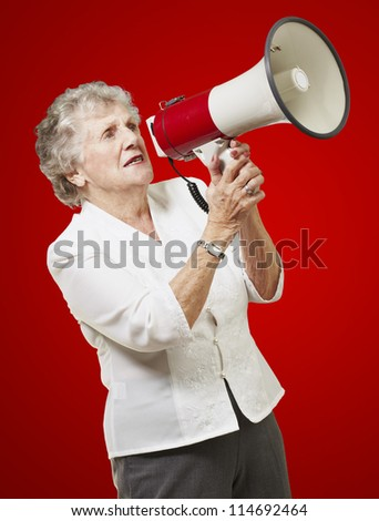 portrait of senior woman holding megaphone over red background - stock photo