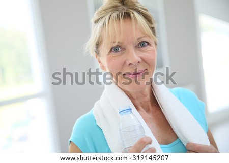 Portrait of senior woman in fitness room drinking water