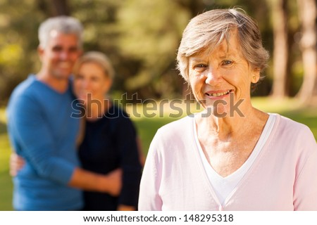 portrait of senior woman in front of middle aged son and daughter-in-law outdoors