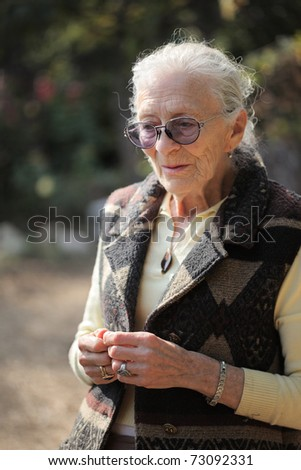 Portrait of senior woman in garden, closeup. - stock photo