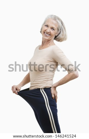 Portrait of senior woman in oversized pants against white background - stock photo
