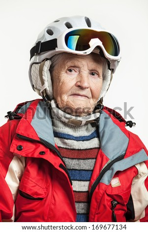 Portrait of senior woman in ski jacket and helmet over white  - stock photo