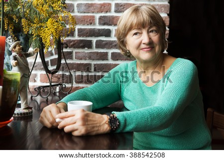 Portrait of senior woman in smart clothes having tea in cafe  - stock photo