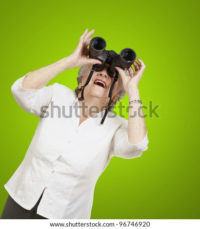 portrait of senior woman looking through a binoculars against a green background - stock photo