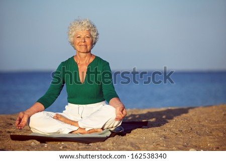 Portrait of senior woman meditating on sandy beach. Smiling mature woman exercising on seashore with copyspace. Meditation, yoga and relaxation concept - stock photo