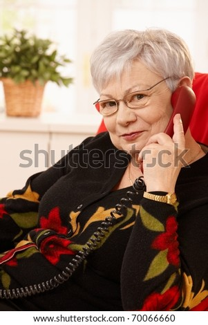 Portrait of senior woman on landline phone call at home, looking at camera, smiling.?