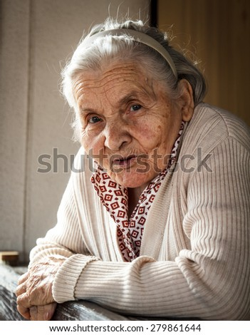 Portrait of senior woman on the porch - stock photo