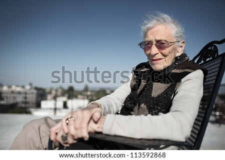 Portrait of senior woman outdoors over blue sky. Shallow DOF, focus on face. - stock photo