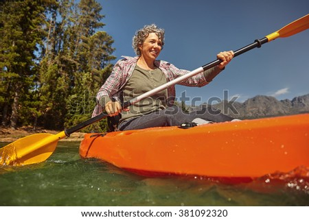 Portrait of senior woman paddling in a lake. Happy mature caucasian woman canoeing on summer day. - stock photo
