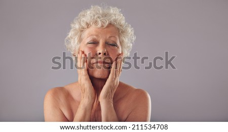 Portrait of senior woman pampering her face against grey background. Natural woman touching her face. - stock photo