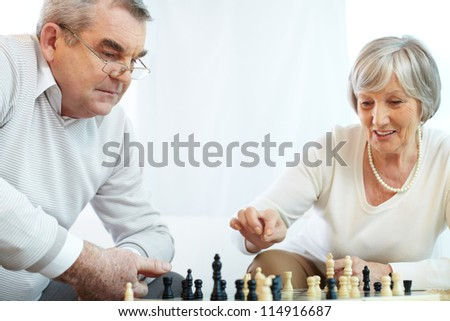 Portrait of senior woman pointing at chess-man while playing chess at leisure with her husband near by