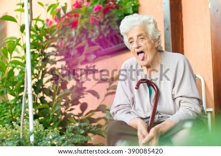 Portrait of senior woman poking out tongue - stock photo