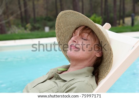Portrait of senior woman relaxing in long chair