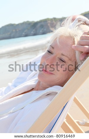 Portrait of senior woman relaxing in longchair - stock photo