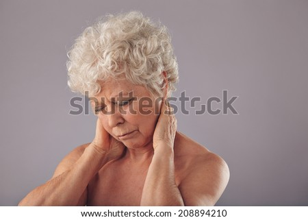 Portrait of senior woman rubbing her sore neck against grey background. Old woman suffering from neck. Discomfort with sore neck. - stock photo