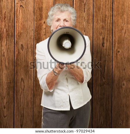 portrait of senior woman screaming with megaphone against a wooden wall - stock photo