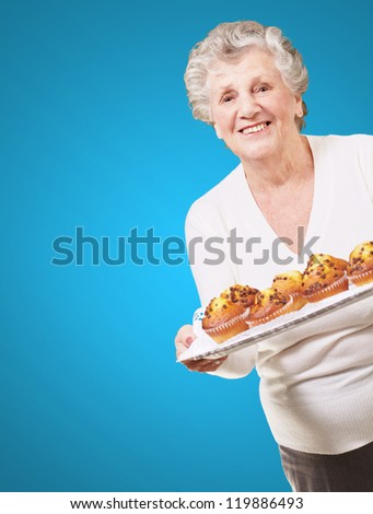portrait of senior woman showing a chocolate muffin tray over blue background
