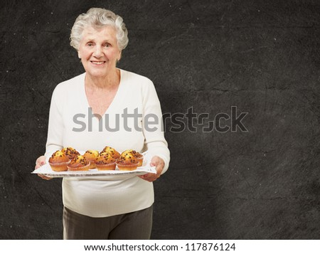 portrait of senior woman showing homemade muffins against a grunge wall - stock photo
