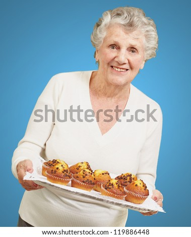 portrait of senior woman showing homemade muffins over blue - stock photo