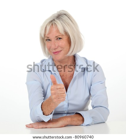 Portrait of senior woman showing thumb up - stock photo