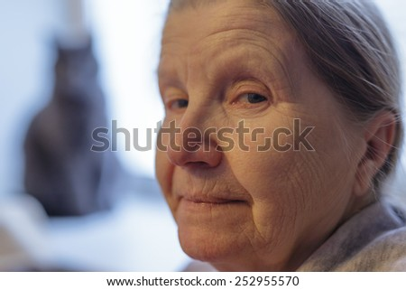portrait of senior woman siting near the window - stock photo