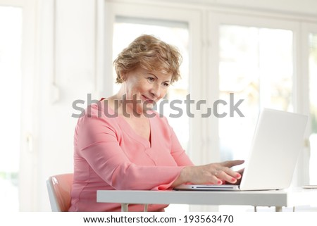 Portrait of senior woman sitting at desk and working on laptop.  - stock photo