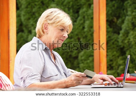 Portrait of senior woman sitting at garden with her laptop. Smiling grandmother holding bank card in her hand while enjoys the convenience of banking online. - stock photo