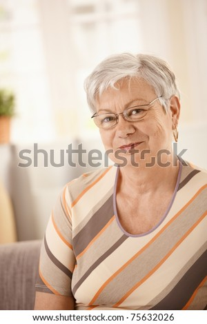 Portrait of senior woman sitting on sofa at home, looking at camera, smiling.? - stock photo