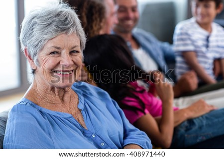 Portrait of senior woman smiling and family sitting in background