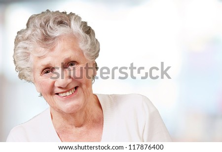 portrait of senior woman smiling over abstract background
