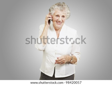 portrait of senior woman talking on a mobile over a grey background