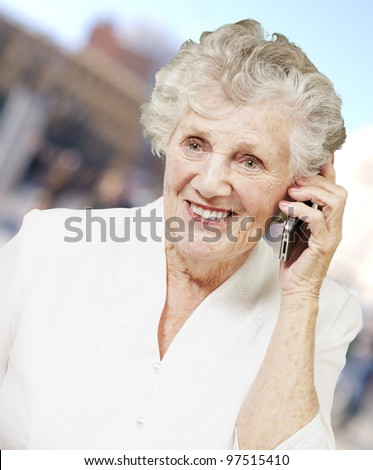 portrait of senior woman talking on mobile at city - stock photo