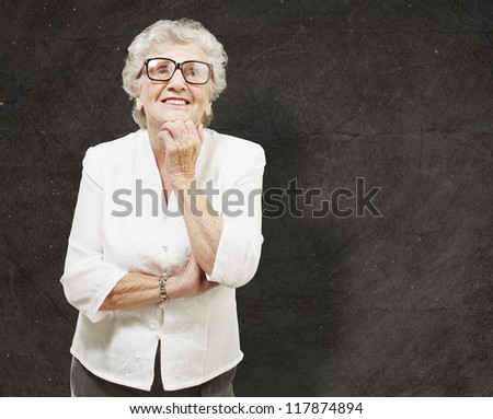 portrait of senior woman thinking and looking up against a grunge wall - stock photo