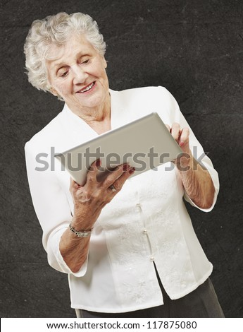 portrait of senior woman touching digital tablet against a grunge wall - stock photo