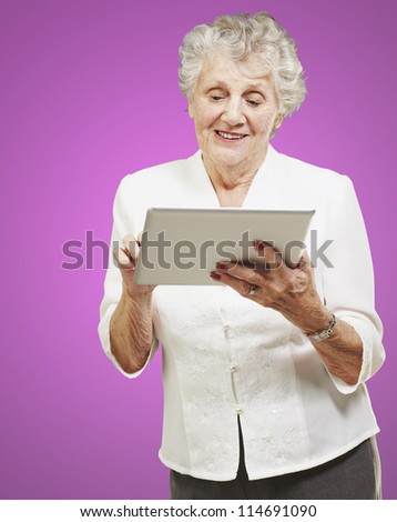 portrait of senior woman touching digital tablet over pink background - stock photo