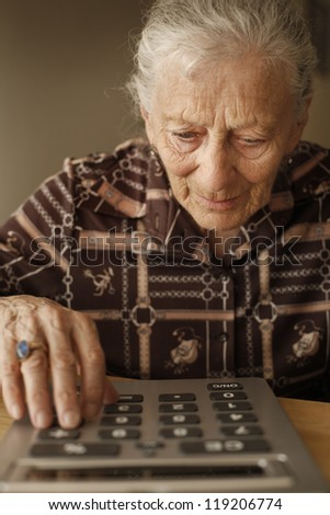Portrait of senior woman using big calculator - stock photo