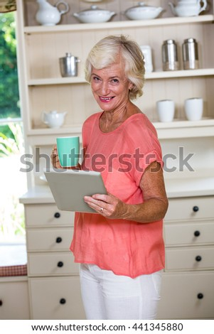 Portrait of senior woman using digital tablet while having coffee in kitchen - stock photo