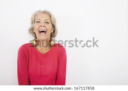 Portrait of senior woman wearing Christmas ornaments over white background - stock photo
